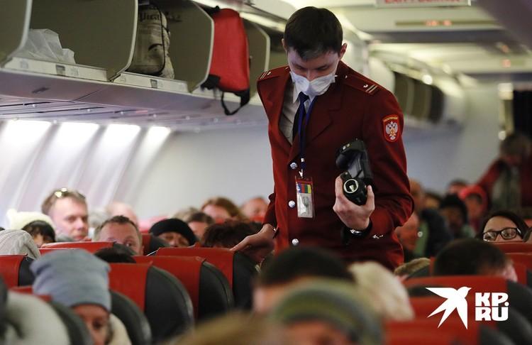 Сотрудник Роспотребнадзора в салоне самолёта, прибывшего из Китая.