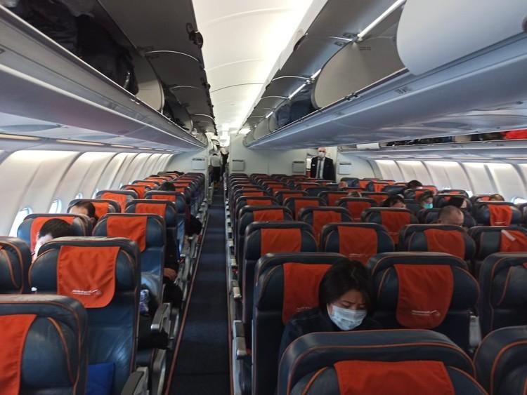 Огромный самолет в Пекин заполнен едва на треть.