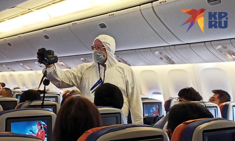 Сначала врачи в скафандрах обошли весь самолет и смерили температуры