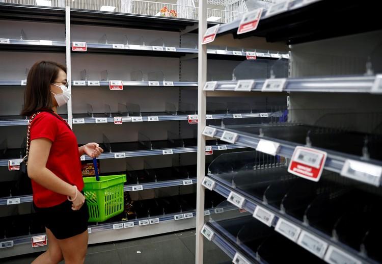 Покупатель у пустых полок в магазине Сингапура.