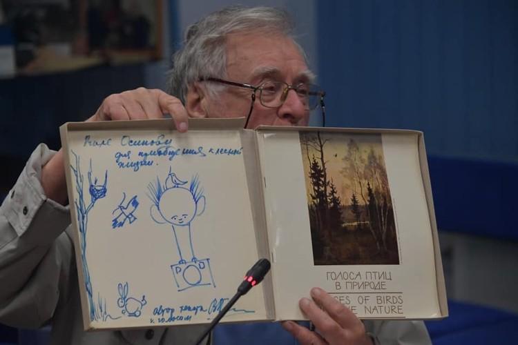 Валентин Осипов держит в руках подарок с дарственной надписью Василия Пескова.