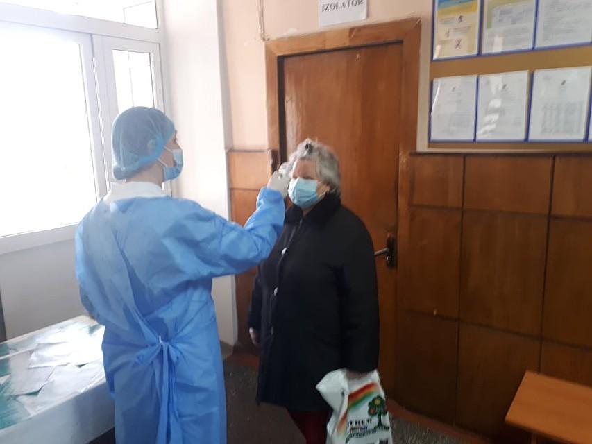Всем посетителям поликлиники сразу же начинают измерять температуру. Фото: Леонид РЯБКОВ