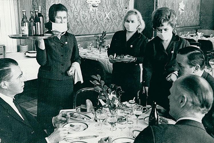 """Фото, сделанное в 1969-м году, как будто из сегодняшней жизни. Официантки ресторана """"Националь"""" в Москве обслуживают клиентов, надев маски. Фото: из коллекции Александра Васильева."""