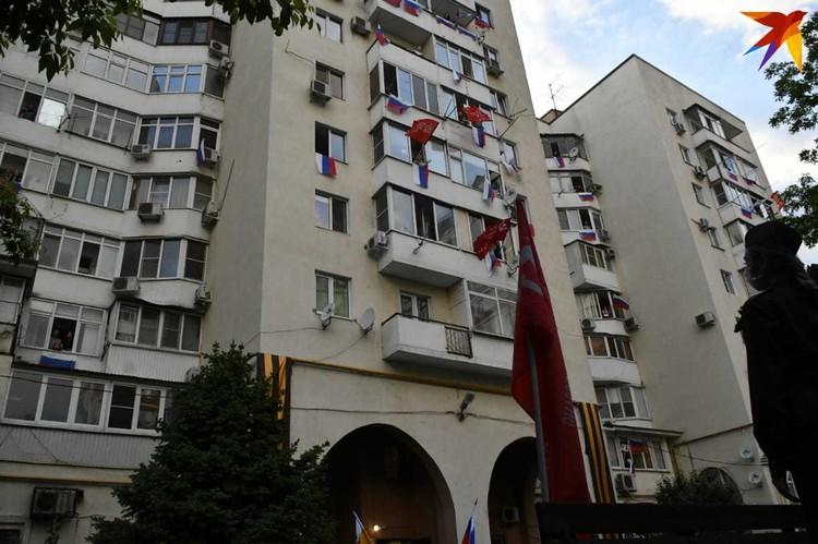 Люди вывесили флаги на балконе