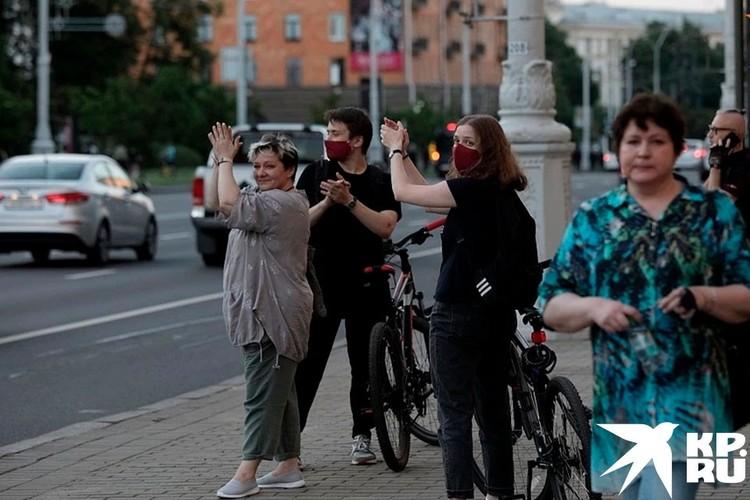 Люди аплодируют проезжающим машинам