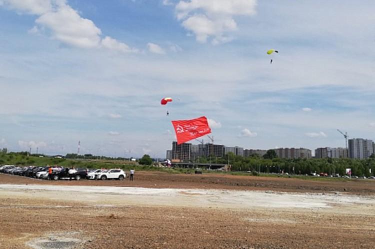 Парашютисты развернули в небе над площадью огромную копию Знамени Победы площадью 250 квадратных метров. Фото: Администрация Кемерова