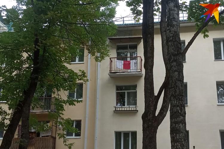Импровизированный флаг из белой и красной одежды на балконе по пути колонны.