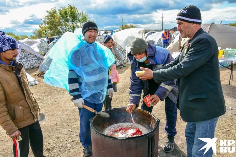 Жители лагеря готовят узбекский плов