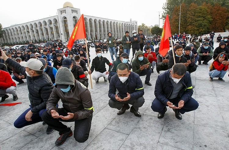 Участники митинга молятся на площади в центре Бишкека, октябрь 2020 г.