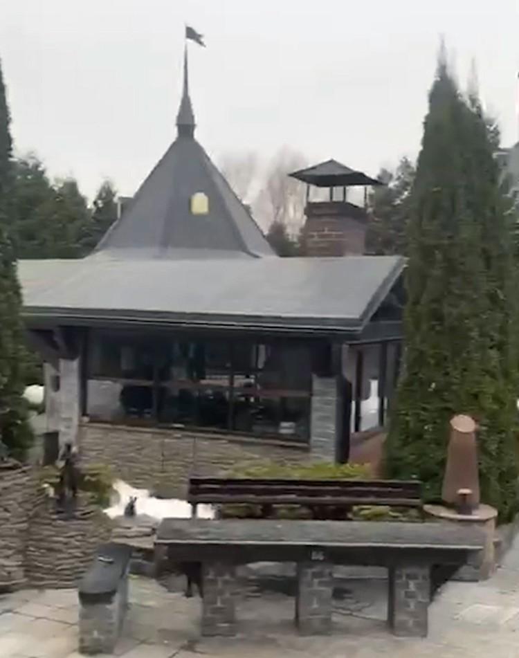 Рядом на участке стоит обеденная зона с панорамными окнами и трубой, очевидно, для гриля.