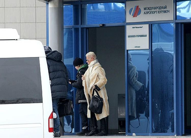 Мари Фредрикссон выходит из здания аэропорта с сыном
