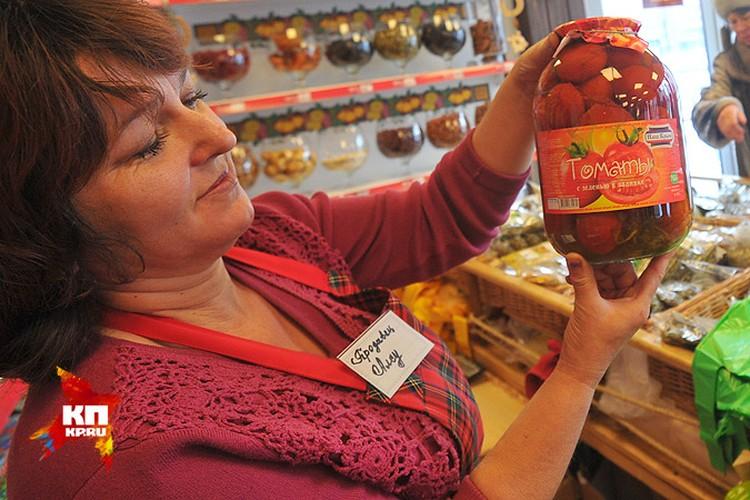 Продавец Алсу демонстрирует банку с крымскими томатами